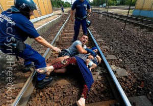 Syrian couple protecting their child from Hungarian police trying to drag the family back into the internment camp for Syrian refugees