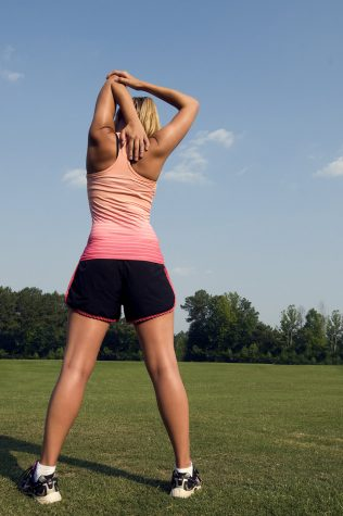 15320-a-healthy-young-woman-stretching-before-exercise-outdoors-pv