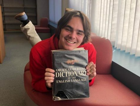 Nolan Wollum poses with a dictionary for his annual slang article.