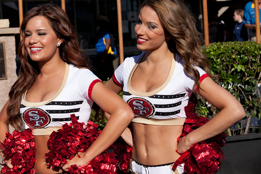 The two 49ers cheerleaders smile after a win at their San Fransisco stadium.
