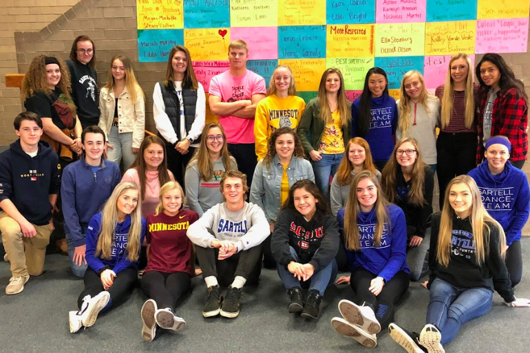 Quarter 1 yearbook staff posing in front of the wall advertisement.