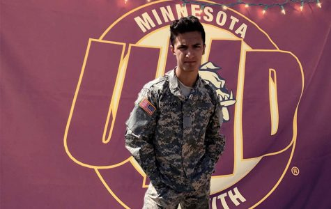 Tyler standing in front of a UMD flag in his uniform.