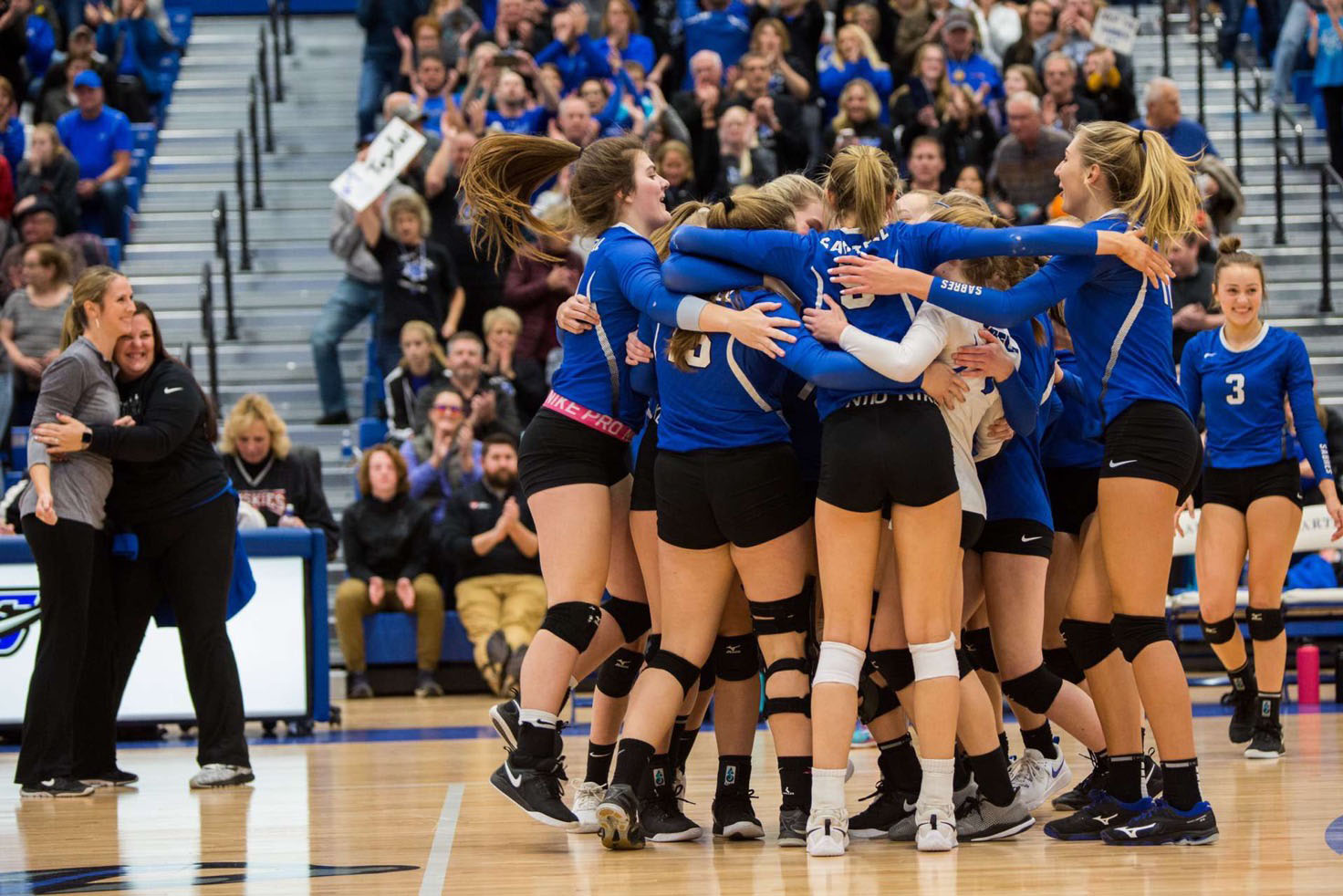 The volleyball team and coaches celebrating after huge victory in the sections semifinals against Alexandria.