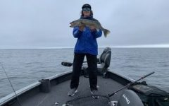 Sunder O'Hara holding a walleye during a rainy day last year
