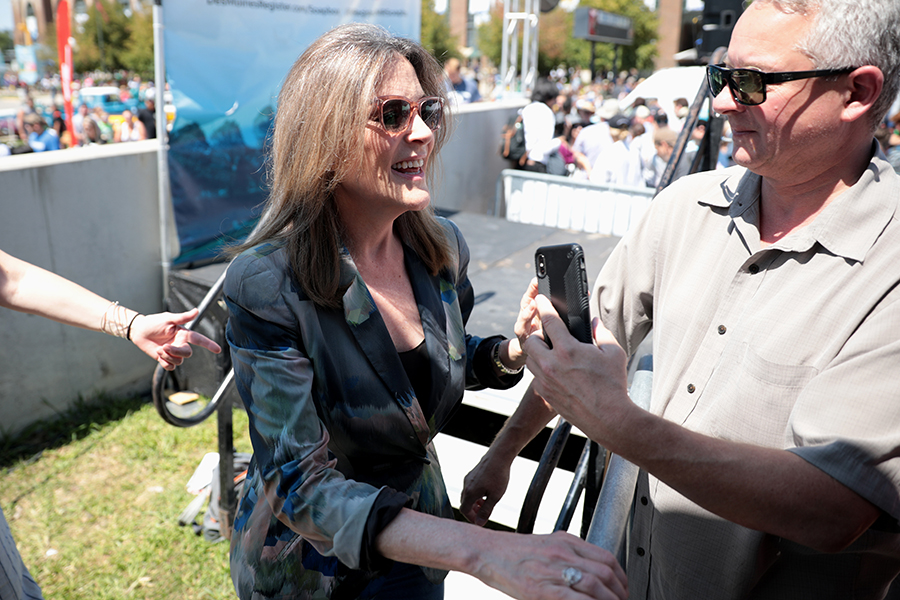 Marianne Williamson shaking hands and answering questions from the people that support her