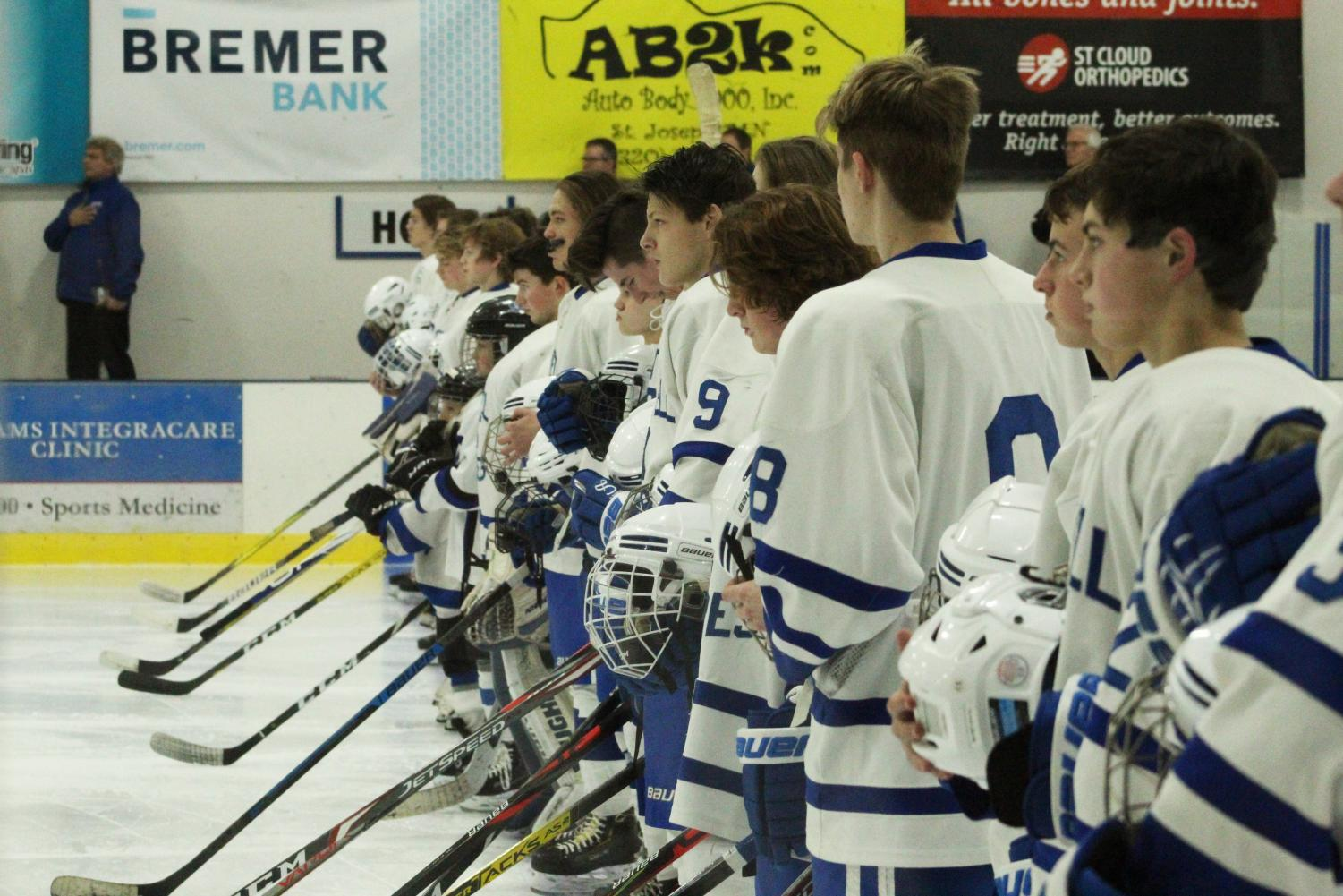 The Sartell boys' hockey team stands at attention during the National Anthem.