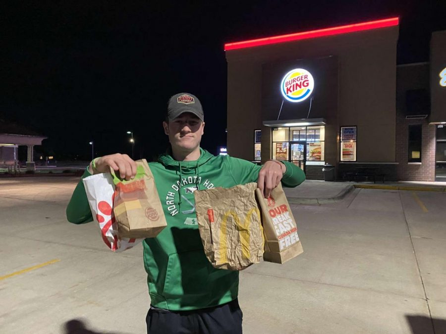 Senior Michael Webster is holding bags from all the spicy nuggets that were in the review, ignore the Chick-fil-A one (from left to right - Burger King, McDonald's, and Wendy's)!