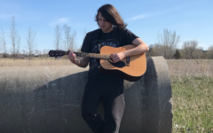 I am playing guitar in a field near the Coborns on Pinecone.