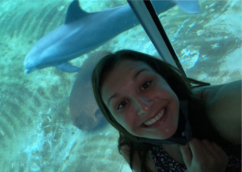 Kaelin Coffin taking a picture on vacation with dolphins.