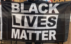 Student holds black lives matter flag before walking out of the building.